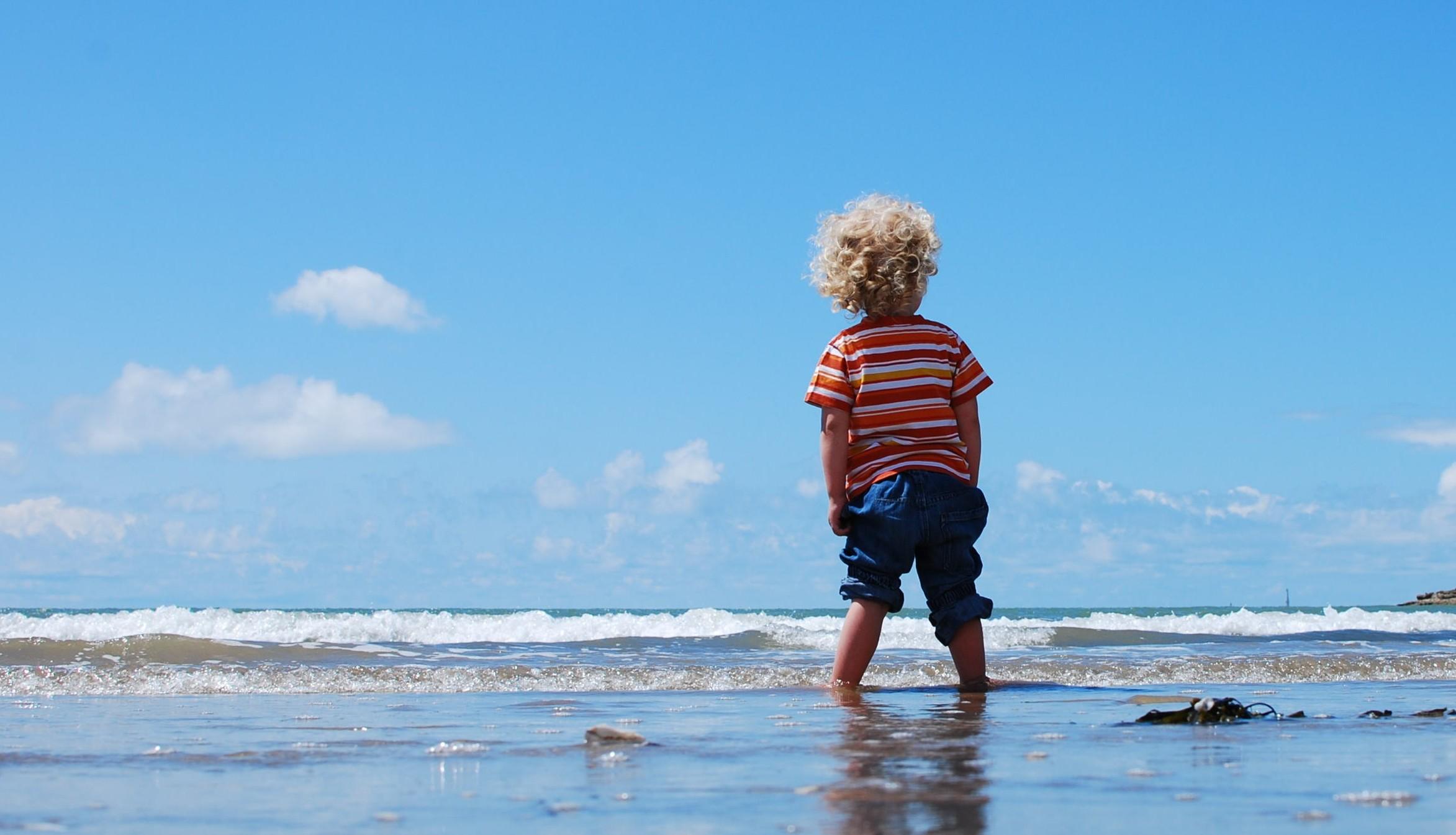 child feet in water beach